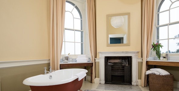 Bedroom 5 en-suite octagonal turret bathroom with roll-top bath and French console basin